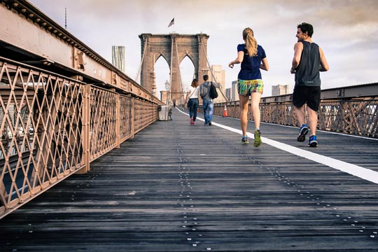 People jogging on a bridge